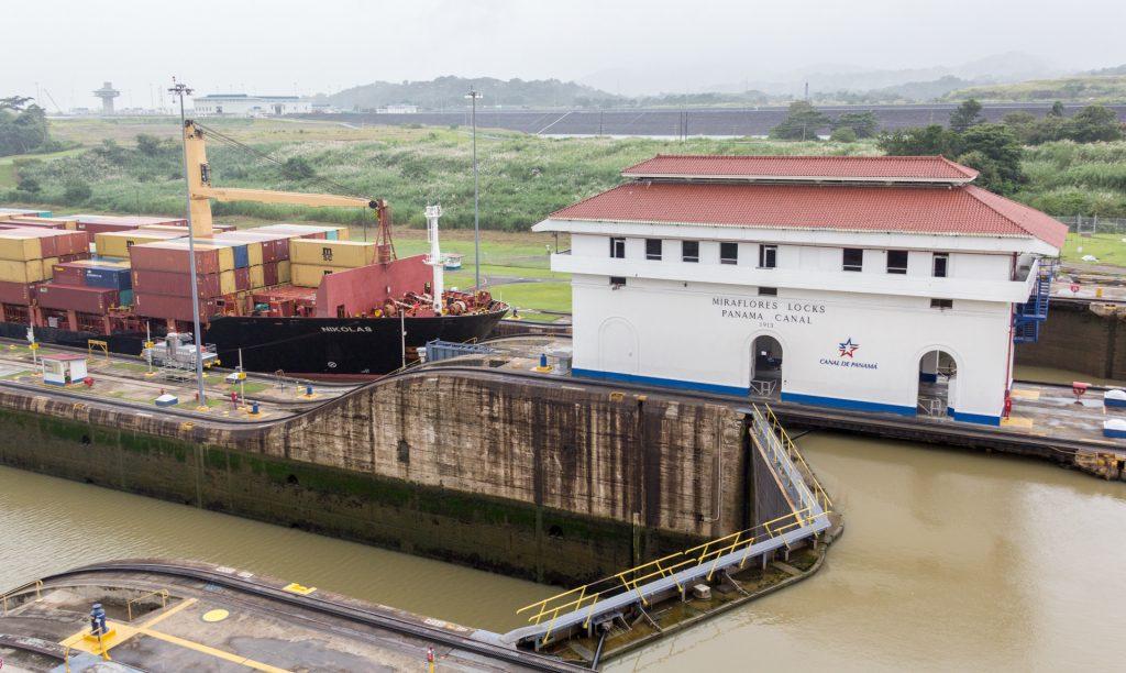 Treidellokomotiven ziehen einen Frachter in die Schleuse